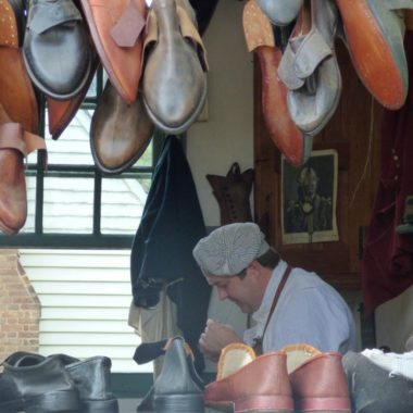An authentic shoemaker works on his wares