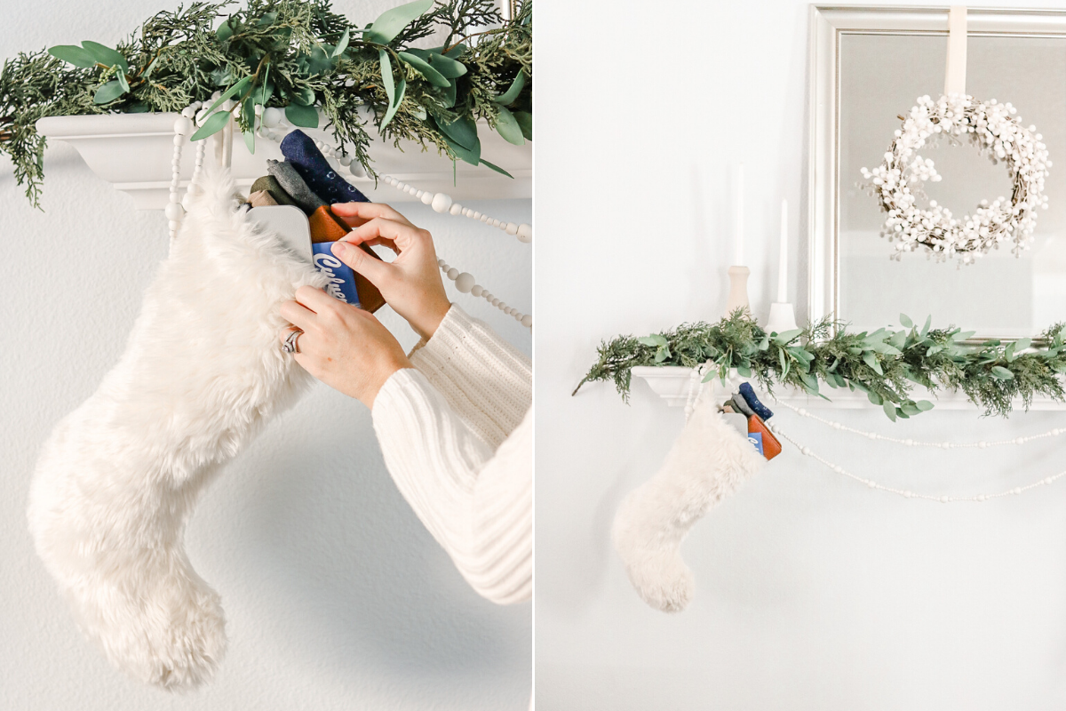 white fur stocking full of stocking stuffers for men on white mantle with greenery garland
