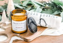 balsam fir candle in amber jar sitting next to sugar cookie printed kitchen towel on wood cutting board