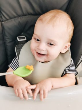 7 month old boy smiling with green baby spoon with sweet potato