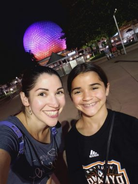 Mom and daughter smiling with Epcot Spaceship Earth lit up in shades of purple behind them