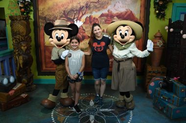 Mom and daughter smiling with Mickey and Minnie Mouse at Disney's Animal Kingdom