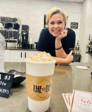 A delicious latte with whipped cream and a smiling mom behind it!