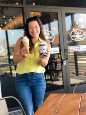Smiling mom in a yellow blouse and jeans holding two coffees!
