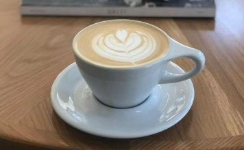 Latte art in a simple white coffee cup and saucer in front of a stack of books on top of a coffee table.